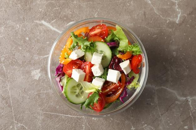 Ciotola di vetro con insalata fresca su gray