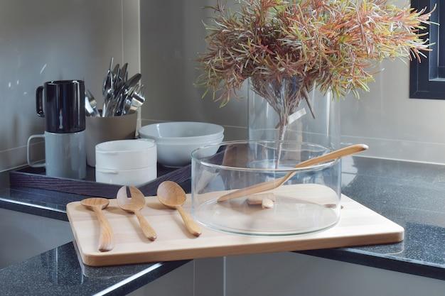 Ciotola di vetro con l'utensile di legno sul vassoio di legno nella cucina