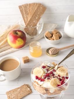 Ciotola di vetro con muesli e yogurt con banana, semi di melograno.
