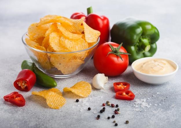 Ciotola di vetro con patatine fritte con paprika e peperoncino. pepe rosso e verde della paprica con il pomodoro e la salsa piccante calda.
