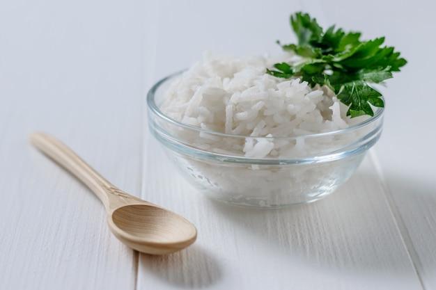 Ciotola di vetro con riso a grani lunghi e prezzemolo e cucchiaio di legno sulla tavola di legno bianca.