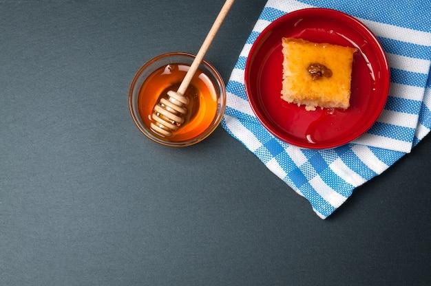 Ciotola di vetro di miele naturale con stecca e torta dolce. sul tavolo rustico in pietra nera.