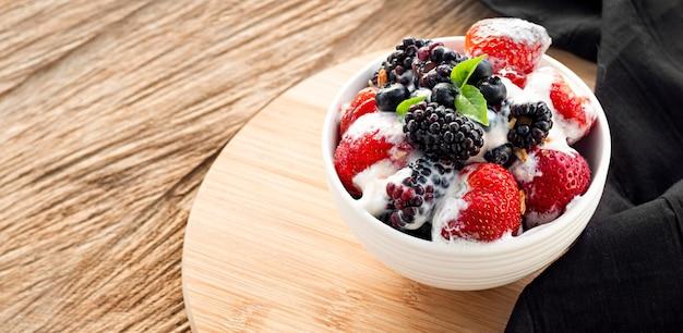 Ciotola di yogurt ad alto angolo sulla tavola di legno