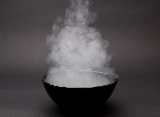 Ciotola di zuppa calda sul nero