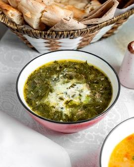 Ciotola di zuppa di erbe guarnita con yogurt