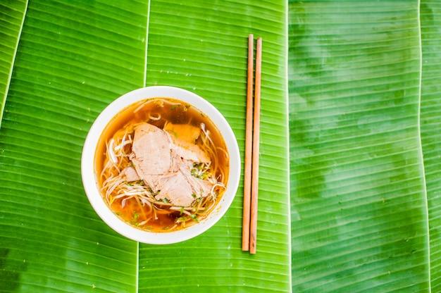 Ciotola di zuppa di manzo vietnamita tradizionale pho bo su sfondo di foglia di banana.