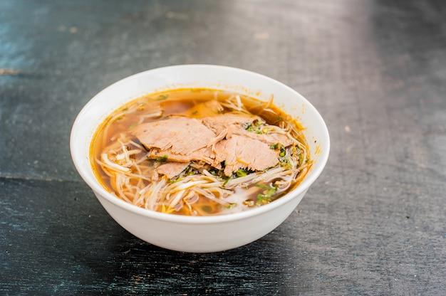 Ciotola di zuppa di manzo vietnamita tradizionale pho bo sullo sfondo di legno vecchio scuro