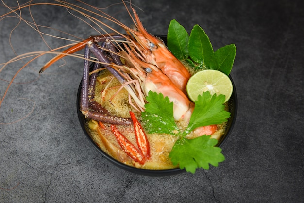 Ciotola di zuppa piccante di gamberi con ingredienti di spezie - frutti di mare cotti con tavolo da pranzo di zuppa di gamberi cibo tailandese tradizionale asiatico, tom yum kung