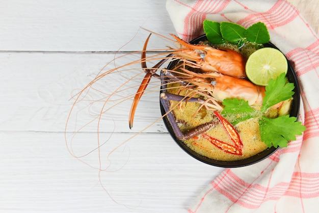 Ciotola di zuppa piccante di gamberi / frutti di mare cotti con tavolo da pranzo di zuppa di gamberi e spezie ingredienti cibo tailandese tradizionale asiatico, tom yum kung