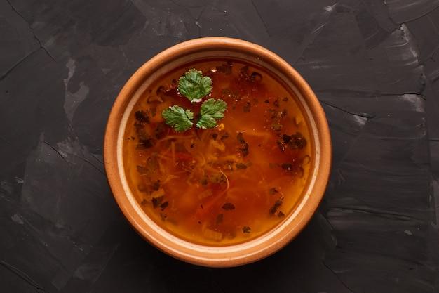 Ciotola di zuppa tradizionale borscht sul tavolo nero. disteso.