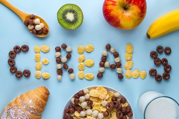 Ciotola e cucchiaio con palline di cioccolato secco, anelli, corn flakes, bicchiere di latte, cornetto e frutta fresca matura per una sana colazione a base di cereali in fibra. concetto di cereali