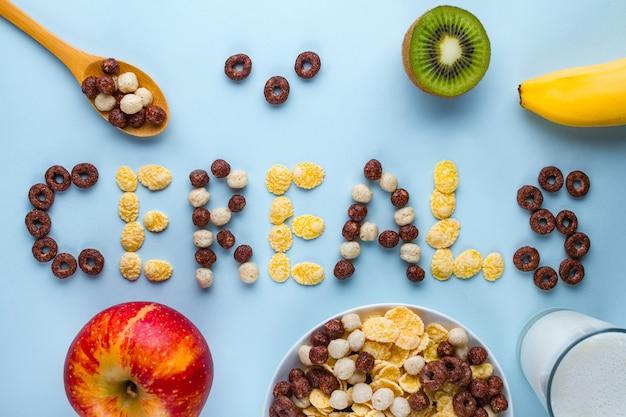 Ciotola e cucchiaio con palline di cioccolato secco, anelli, corn flakes, bicchiere di latte e frutta fresca matura per una sana colazione a base di cereali in fibra. concetto di cereali