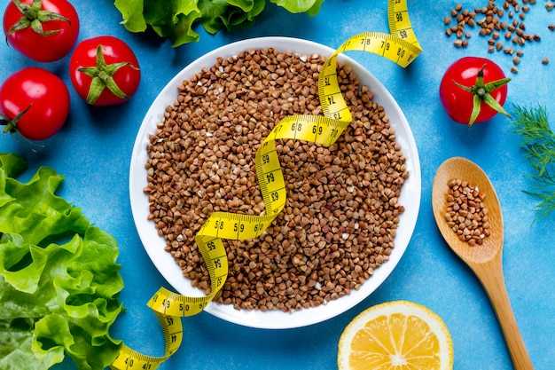 Ciotola e cucchiaio di grano saraceno con verdure mature fresche e nastro di misurazione giallo