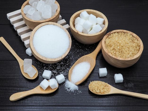 Ciotola e cucchiaio di legno con lo zucchero cubo su fondo di legno scuro.