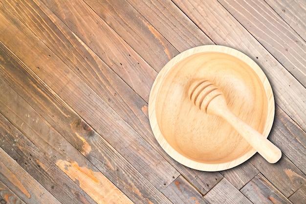 Ciotola e merlo acquaiolo di legno sul fondo di legno di struttura