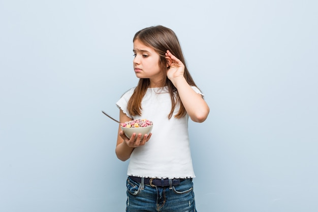 Ciotola holdingcereal della piccola ragazza caucasica che prova ad ascoltare un gossip.
