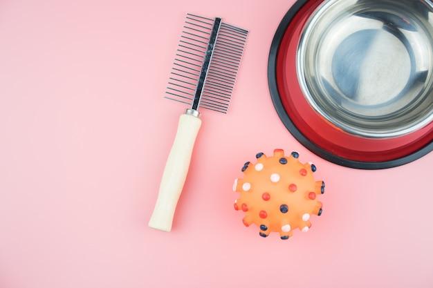 Ciotola in acciaio inox con pettine e palla di gomma su sfondo di colore.