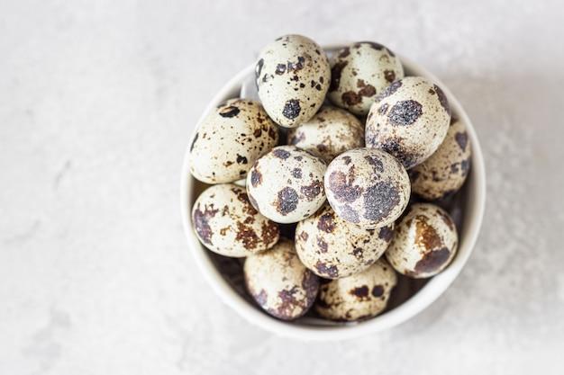 Ciotola in ceramica bianca con uova di quaglia, pietra grigio chiaro