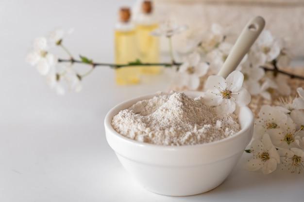 Ciotola in ceramica con polvere di argilla bianca su superficie bianca. ingredienti per maschera o scrub viso e corpo fatti in casa e rametto fresco di fioritura di ciliegie. spa e concetto di cura del corpo.