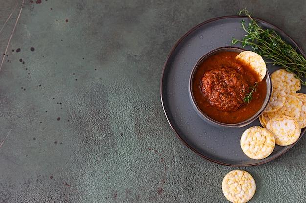 Ciotola in ceramica con salsa di pomodoro piccante, tortilla chips e timo. concetto di cibo messicano.