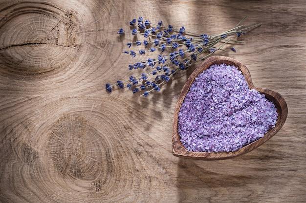 Ciotola in forma di cuore con lavanda asciutta del sale marino sul concetto di trattamento della stazione termale del bordo di legno