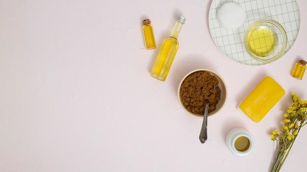 Ciotola macinata a caffè; olio essenziale; batuffolo di cotone; sapone giallo e fiori di limonio su sfondo strutturato