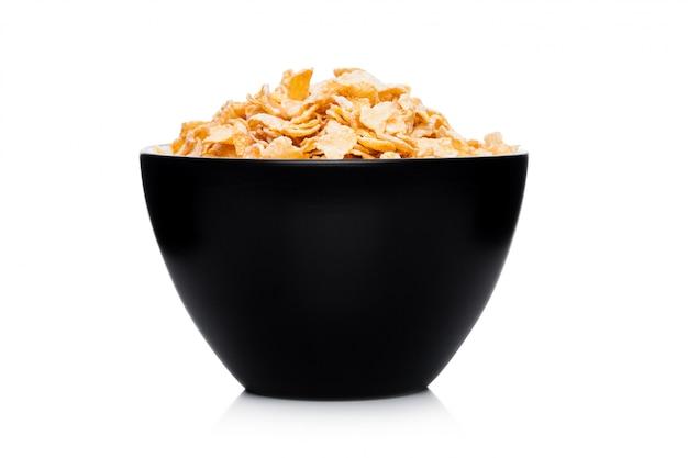 Ciotola nera con i fiocchi di mais organici naturali del cereale del granola su bianco
