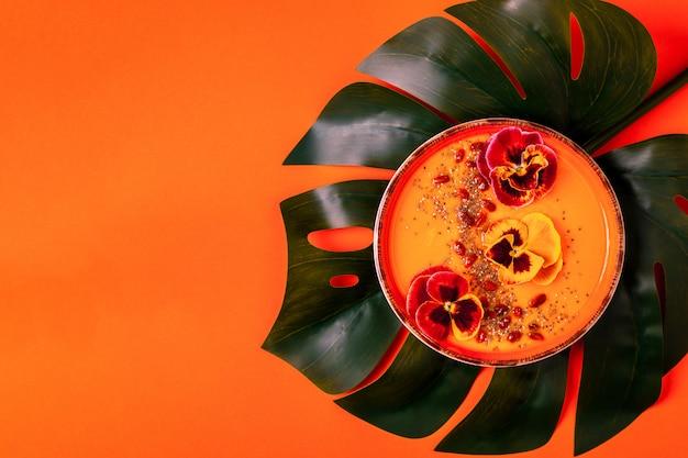 Ciotola per frullato con fiori commestibili di viola del pensiero, semi di chia, bacche di goji