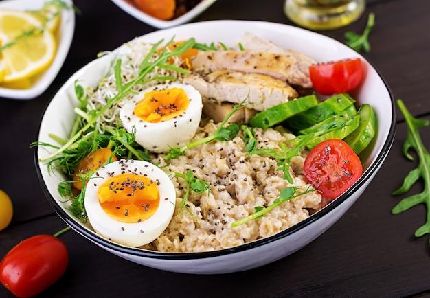 Ciotola per la colazione con farina d'avena, filetto di pollo, pomodoro, lattuga, microgreens e uovo sodo.