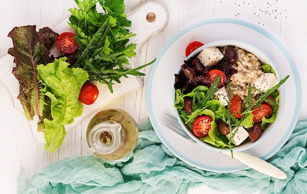 Ciotola per la colazione con farina d'avena, pomodori, formaggio, lattuga e olive. cibo salutare. ciotola di buddha vegetariana