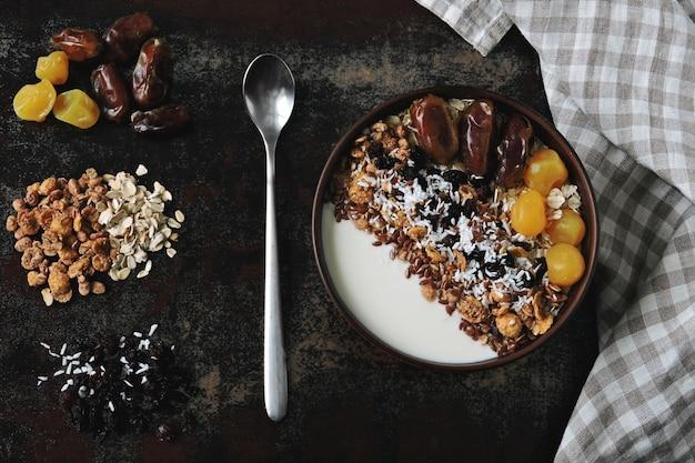 Ciotola per la colazione con yogurt greco, farina d'avena, muesli e frutta secca.