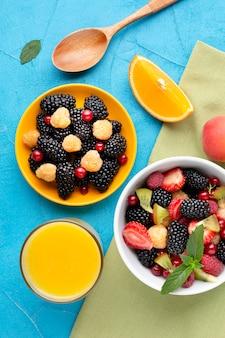 Ciotola piatta di bacche fresche e frutta con bicchiere di succo