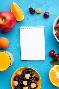 Ciotola piatta di bacche fresche e frutta con blocco note