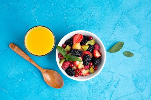Ciotola piatta di bacche fresche e frutta con succo