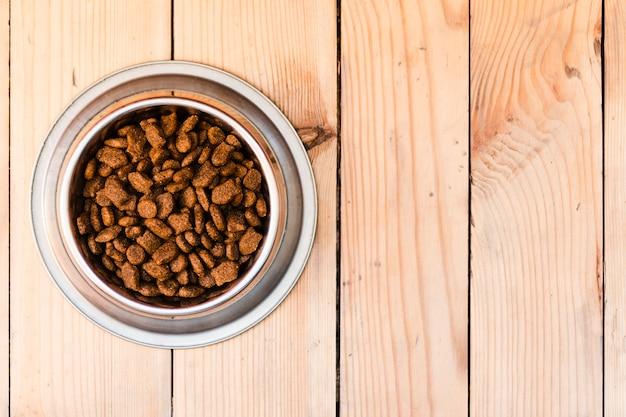 Ciotola piena del cibo per cani su fondo di legno con lo spazio della copia