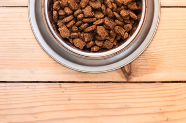 Ciotola piena del cibo per cani su fondo di legno