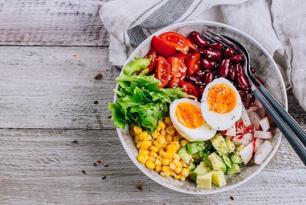 Ciotola pranzo vegano con avocado, uovo, fagiolo rosso, pomodoro, ravanello, mais, insalata di verdure foglie verdi