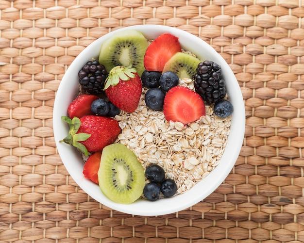 Ciotola ripiena di frutta e cereali piatto disteso