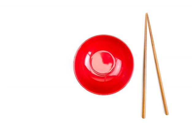 Ciotola rossa con le bacchette e isolata