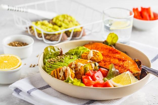 Ciotola vegan rainbow di polpette di verdure, avocado, patata dolce