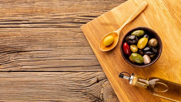Ciotola verde oliva della bottiglia di olio e cucchiaio di legno con lo spazio della copia