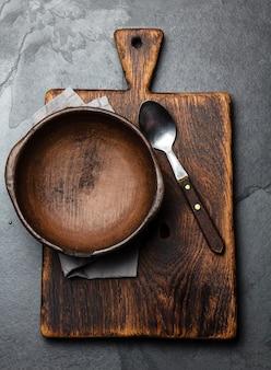 Ciotola vuota d'argilla d'annata sui taglieri