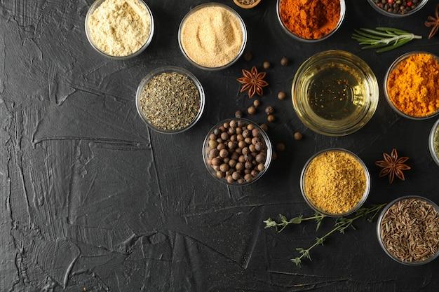Ciotole con differenti spezie ed ingredienti su fondo nero, vista superiore