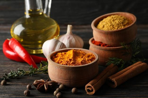 Ciotole con le spezie e gli ingredienti su di legno