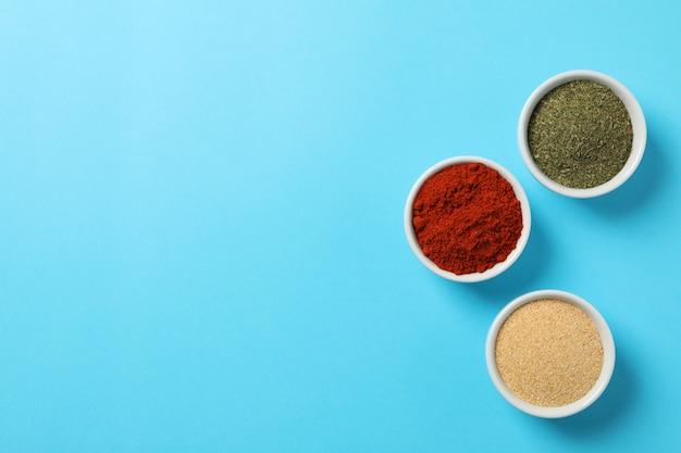 Ciotole con polvere di peperone, aglio e aneto sulla vista blu e superiore