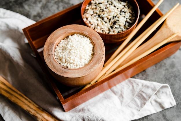 Ciotole con riso e bacchette di legno varie