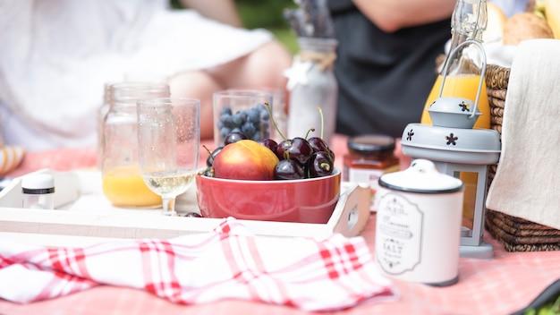 Ciotole di frutta e bicchiere di birra al picnic