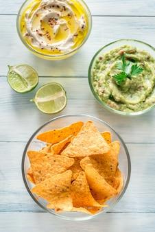 Ciotole di hummus e guacamole con tortilla chips