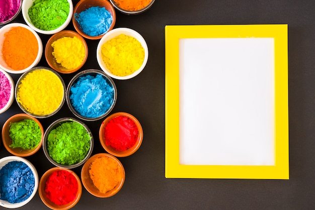 Ciotole di polvere di colore holi vicino alla cornice bianca con bordo giallo su sfondo nero