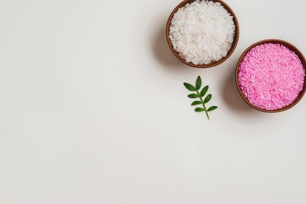 Ciotole di sale rosa e bianco con foglie verdi su sfondo bianco